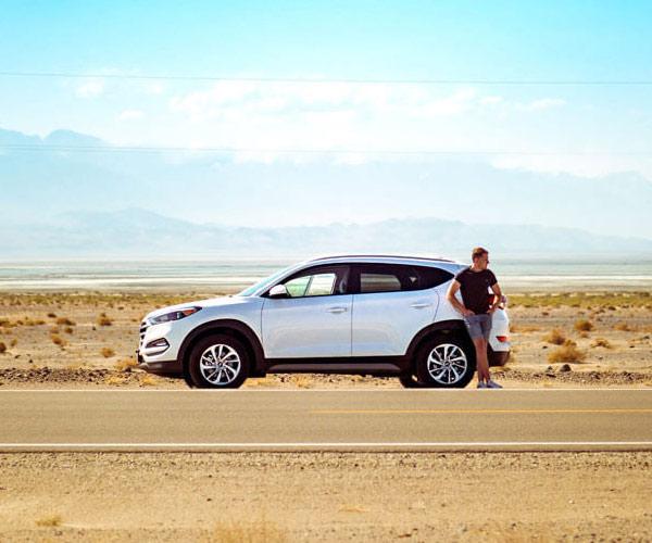 Auto Insurance young man standing on side of road with SUV